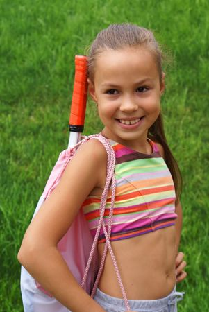 Smiling preteen girl in exersise gear on green grass background photo