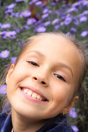 Cheerful preteen girl on purple flower background