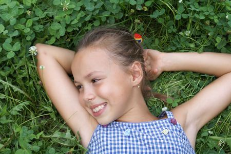 Smiling preteen girl on clover background