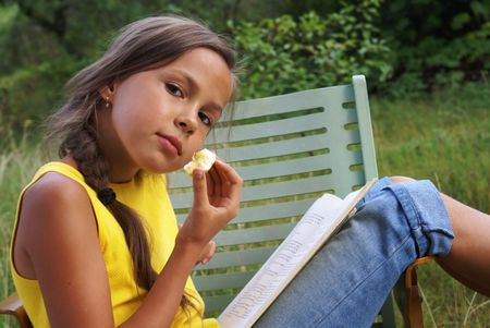 Reading preteen girl on green grass background                 photo