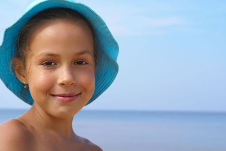preteens beach: Preteen girl on a beach on blue background