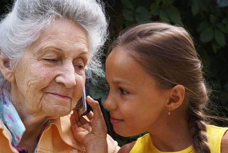 Grand daudhter and her grand mother talk on mobile phone                     photo