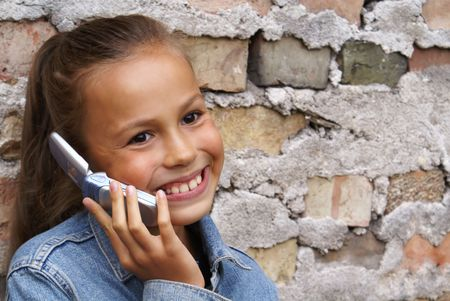 Preteen girl talking on mobile phone on grunge brick wall background