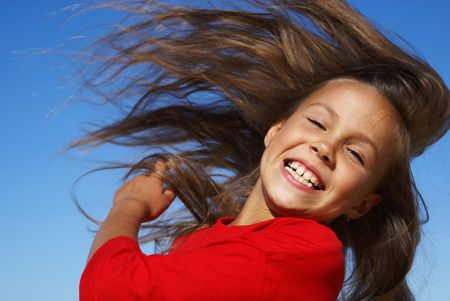 beautiful preteen girl: Preteen girl flipping hair on blue sky background