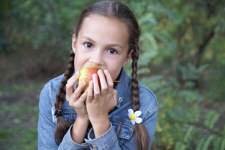 Preteen girl biting a peach on green leaves background                     Фото со стока