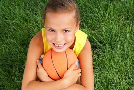 basketball girl: Preadolescente ni�a con el baloncesto de fondo sobre la hierba Foto de archivo