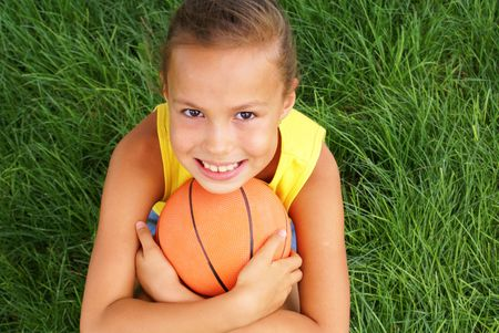 preteen girls: Preteen girl with basketball on grass background