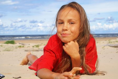 Cheerful preteen girl lying on sea beach                  photo