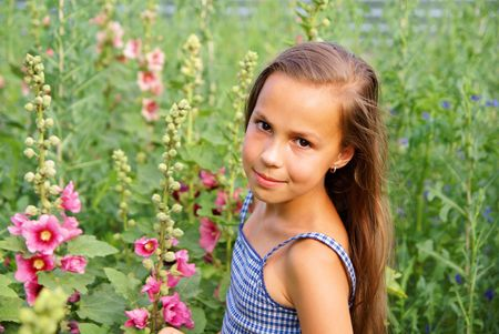 Smiling preteen girl with flowers on green grass background