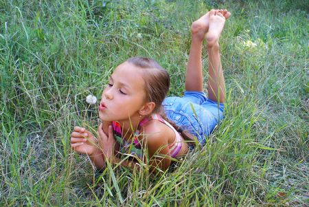 Preteen girl blowing on dandelion in grass background