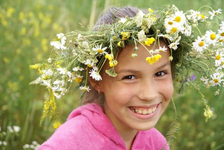 Cheerful preteen girl in field flower garland on green grass background