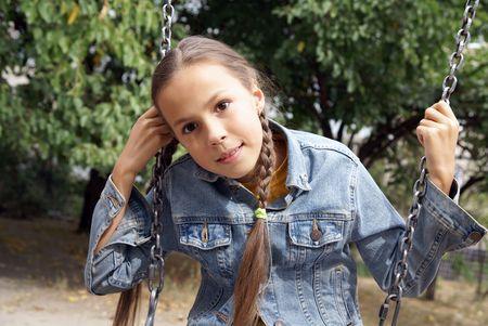 Preteen girl having fun on a swing on playground                photo