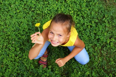 Smiling preteen girl with dandelion  flower on green clover background Фото со стока - 4880523