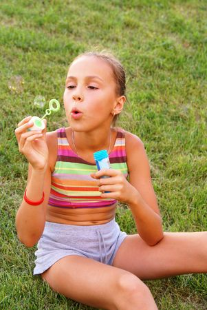 Preteen girl blows bubbles on green grass background          Фото со стока