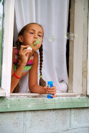 brads: Preteen girl blows bubbles sitting in window