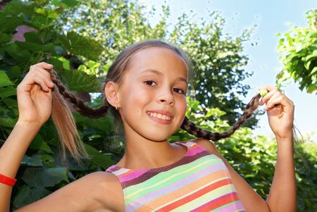 Cheerful preteen girl showing her braids outdoor         photo