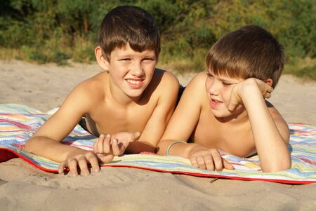preteen boy: Two preteen boys sunbathing on beach                Stock Photo