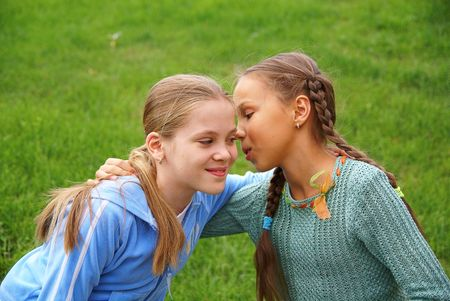 Smiling preteen girls talking outdoors on green grass background