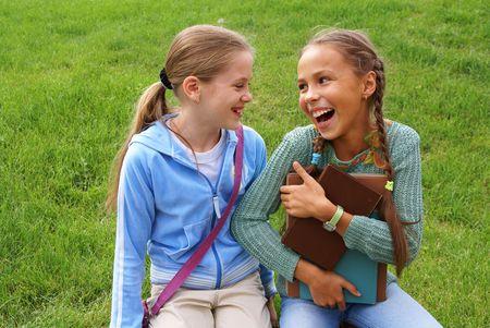 little models: Preadolescente ni�as de la escuela con libros sobre la hierba verde de fondo al aire libre Foto de archivo
