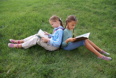 Preteen school girls reading books on green grass background outdoors