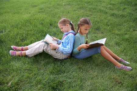 Preteen school girls reading books on green grass background outdoors   photo