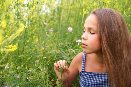 petite: Smiling preteen girl admiring field flowers on grass background Stock Photo