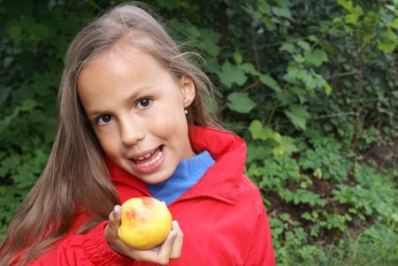 Smiling preteen girl eating a peach