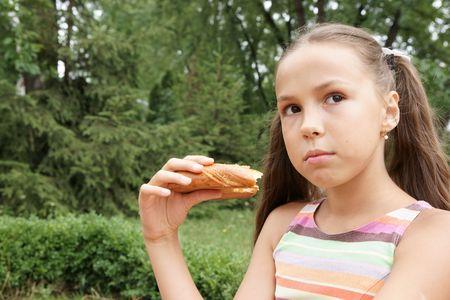 Preteen girl eats bread outdoors