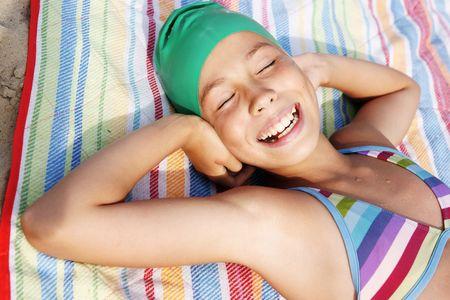 Preteen girl sunbathing on sea beach