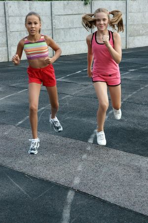 Two preteen girls runnig on track
