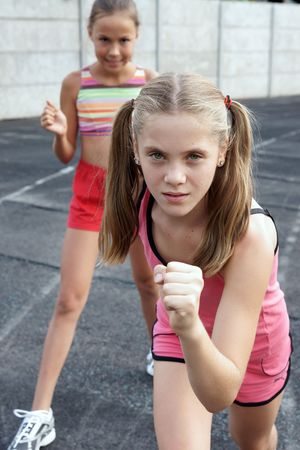 Two preteen girls runnig on track Фото со стока - 5488131