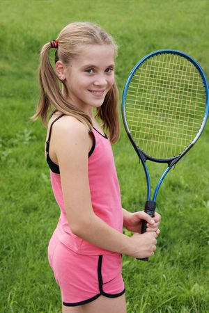Happy teenage girl in sport outfits with tennis racket on green grass background Stock Photo