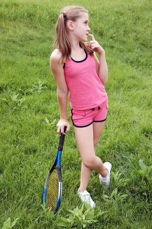 Gelukkig preteen meisje in de sport uitrustingen met een tennisracket op groen gras achtergrond  Stockfoto