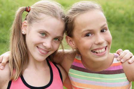 Happy preteen girls friendly hugging on green grass background