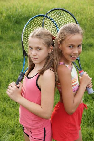 petite: Happy preteen girls in sport outfits with tennis rackets on green grass background