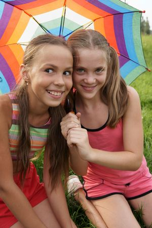 petite: Happy preteen girls in sport outfits with umbrella on green grass background Stock Photo