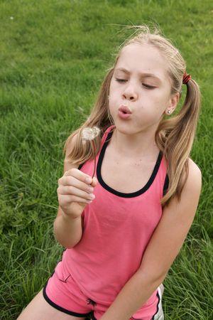 タンポポ緑の草の背景上に 10 代の少女が吹く