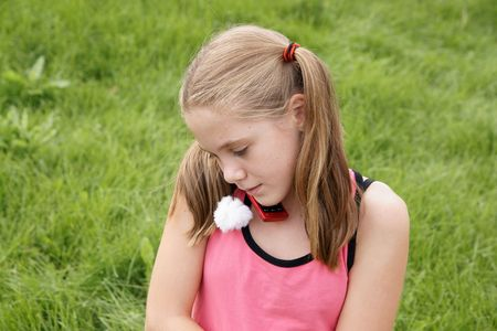 Teenage girl talks on ceellural phone on green grass background photo