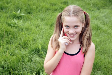 petite: Happy teenage girl talks on ceellural phone on green grass background