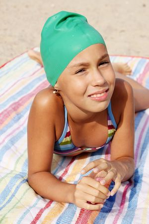 Preteen girl enjoying sun-bath on sea beach