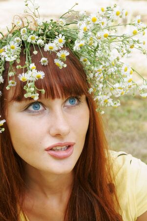Beautiful cheerful girl in field flower garland outdoors