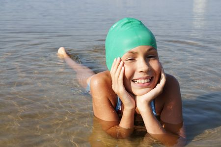 preteens beach: Cheerful preteen girl swimming in sea  Stock Photo