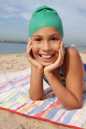 Preteen girl enjoying sun-bath on sea beach photo