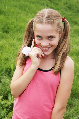 Happy teenage girl talks on cellural phone on green grass background Stock Photo