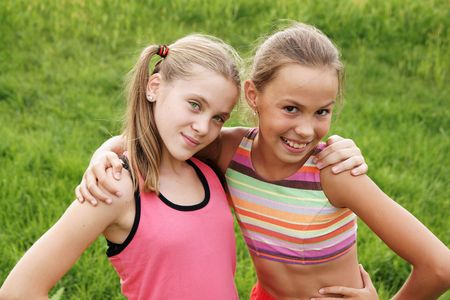 preteen girls: Happy preteen girls friendly hugging on green grass background