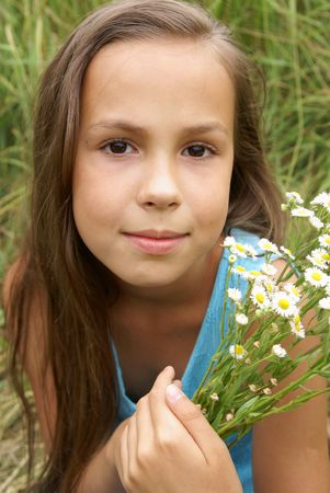 Beautiful preteen girl in blue dress with field flowers outdoors Фото со стока - 5511059