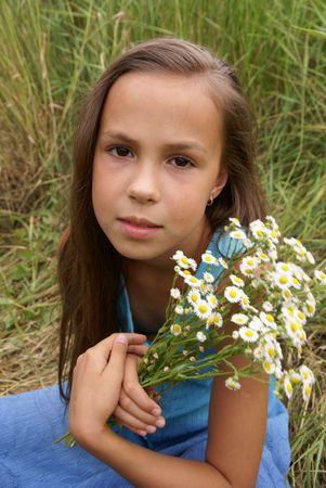 Beautiful preteen girl in blue dress with field flowers outdoors
