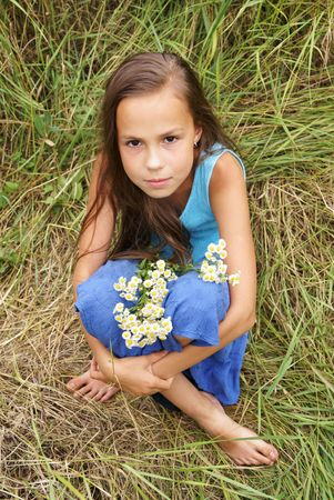 beautiful preteen girl: Beautiful preteen girl in blue dress with field flowers outdoors