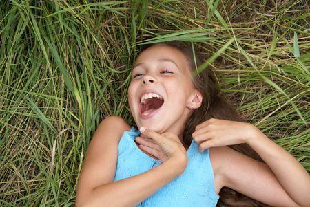 Beautiful preteen girl in blue dress lying on green grass 스톡 콘텐츠