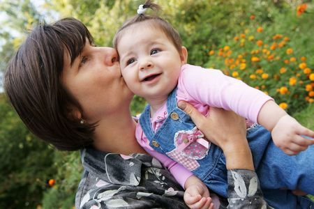 Happy mother kissing baby daughter outdoors photo